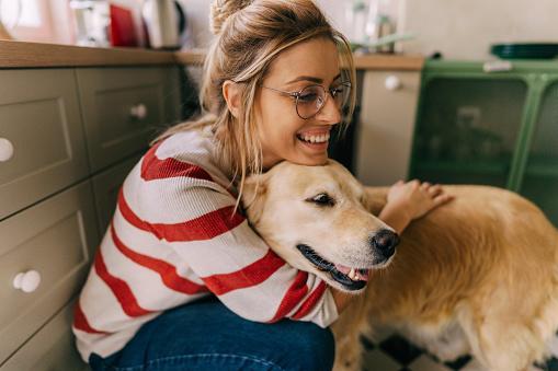 девушка в очках и джемпере с красными полосами обнимает собаку
