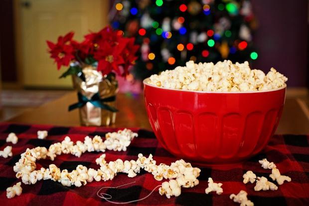 красная тарелка с попкорном рядом со стеклянной вазой с красными цветами