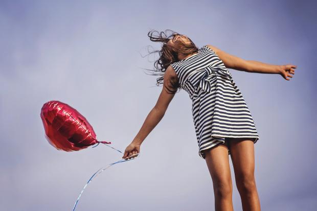девушка с воздушным шариком в прыжке