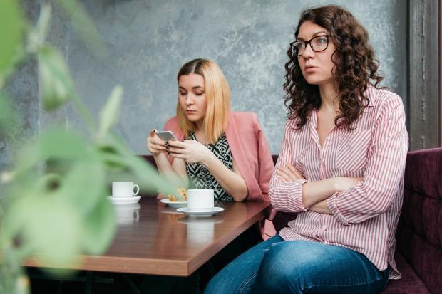 две девушки, одна смотрит в телефон, другая отвернулась