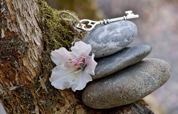 три камня, лежащих друг на друге, цветок и ключ
