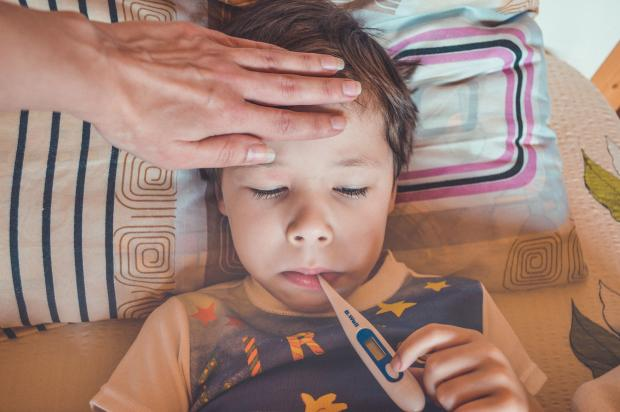 заболевший ребенок держит во рту термометр