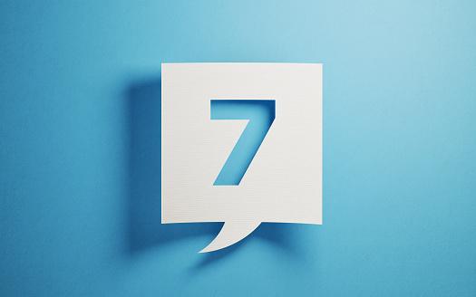 вырезанная из бумаги цифра 7 на голубом фоне