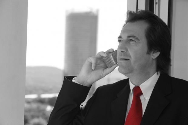 мужчина разговаривает по телефону и смотрит в окно