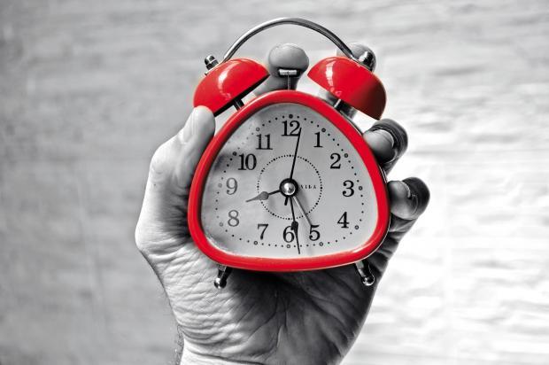красный будильник в руке