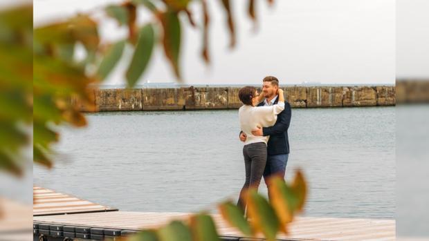 влюбленные стоят в обнимку на берегу осеннего моря