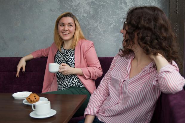 две подруги сидят за столиком в кафе