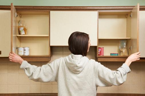 девушка заглядывает на полки подвесных шкафчиков