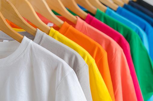 на плечиках висят подобранные по цветовой гамме футболки