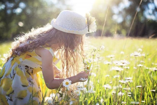 Девочка в ярком платье на поляне нюхает цветы