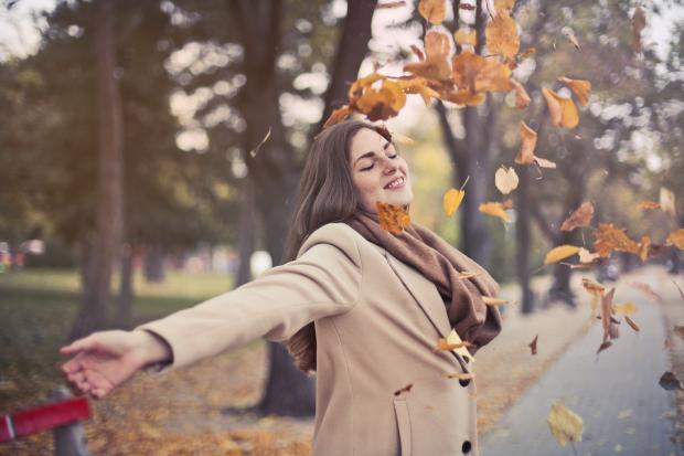 Молодая девушка в осеннем парке бросает листья
