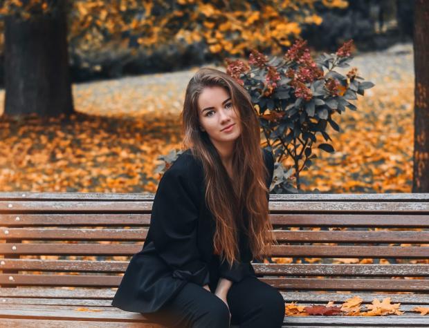 Девушка сидит на скамейке в осеннем парке
