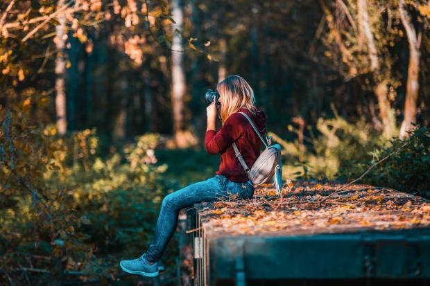 Девушка делает фотографию на природе