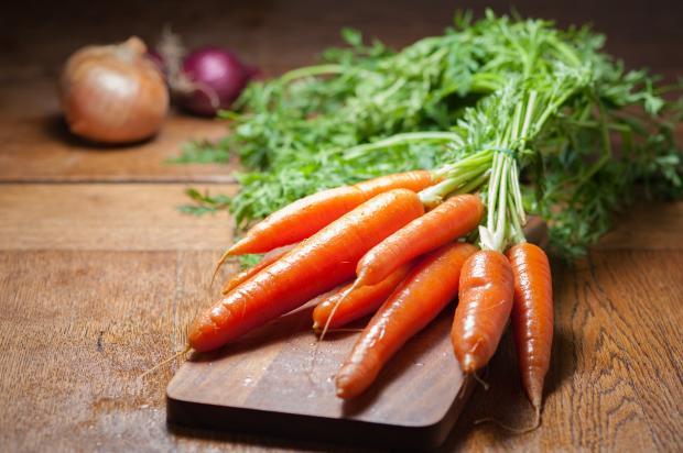 свежая морковь с зелеными листьями на столе