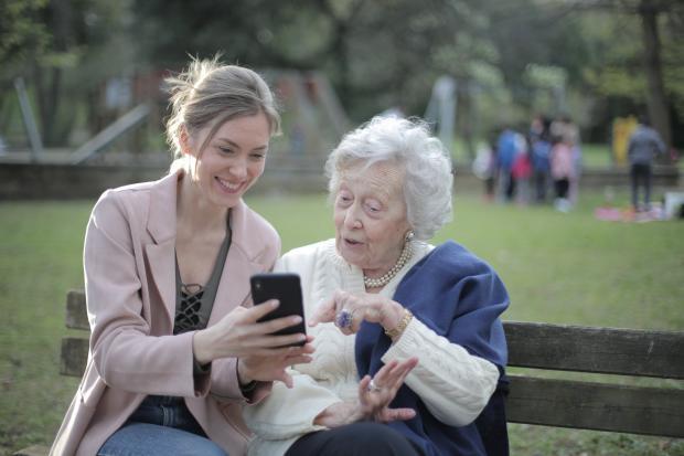 Молодая девушка помогает пожилой женщине