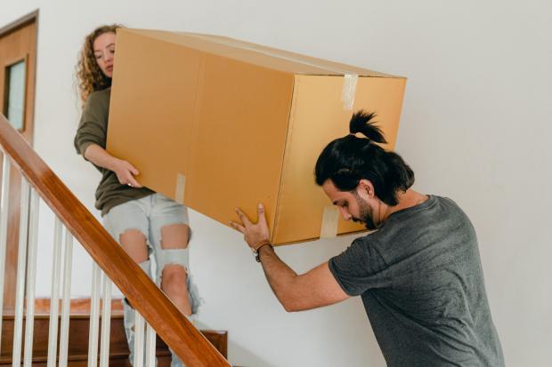 Молодые девушка и парень несут большую картонную коробку