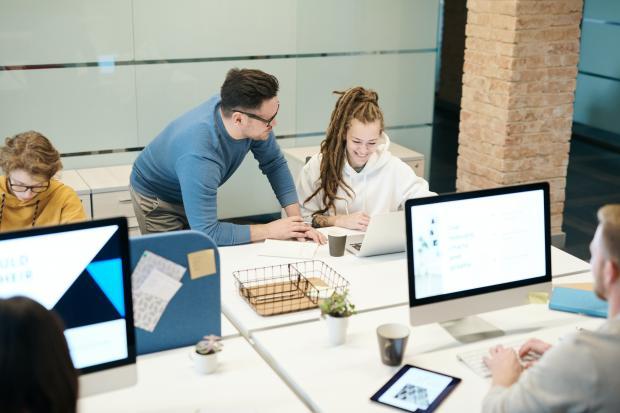 Молодой мужчина помогает девушке за компьютером