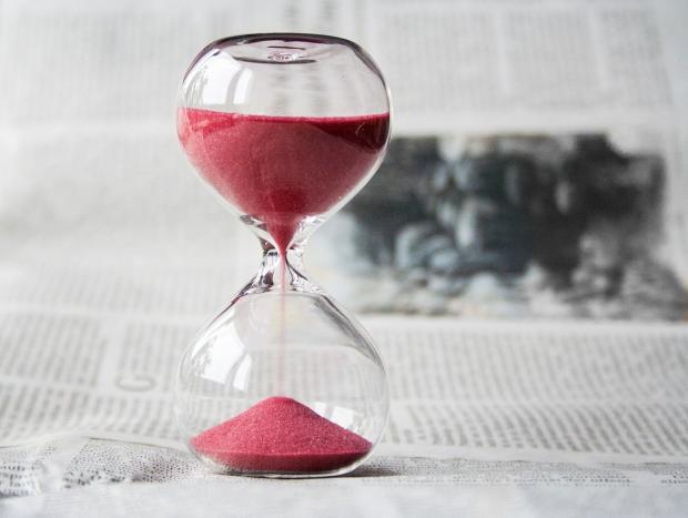 песочные часы с красным песком стоят на газете