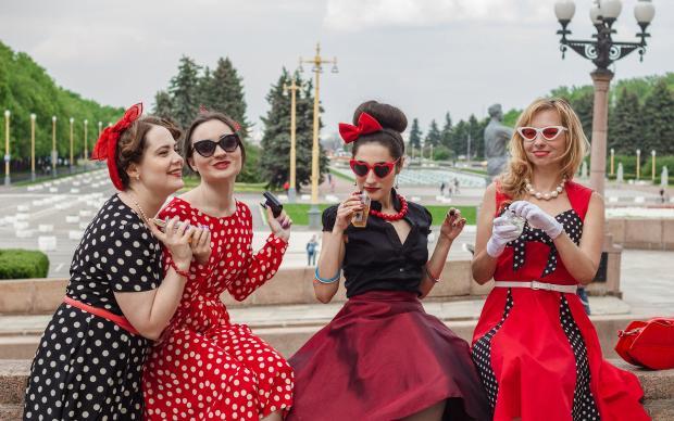 четыре девушки в ретро одежде общаются