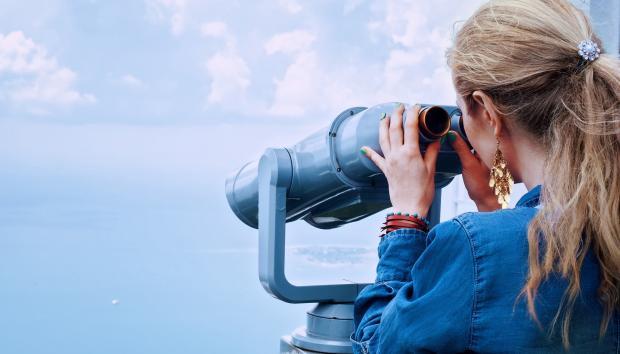 девушка в бинокль смотрит на море
