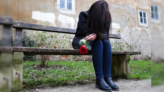девушка с длинными черными волосами и опущенной головой сидит на скамейке с красной розой в руках