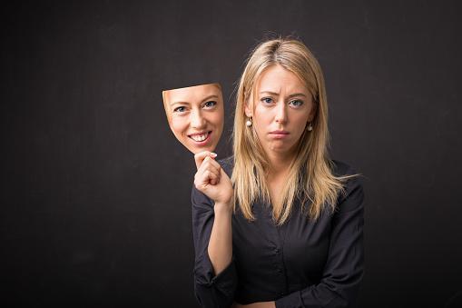 грастная белокурая девушка держит в руках маску с веселым выражением лица