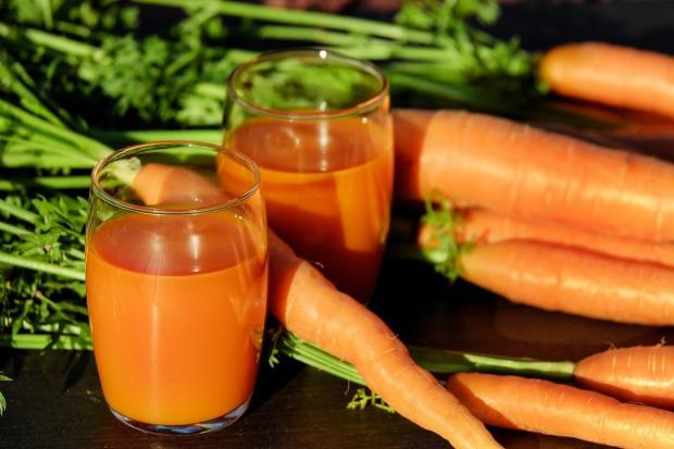 на столе рядом со свежей морковью стоят два стакана морковного сока