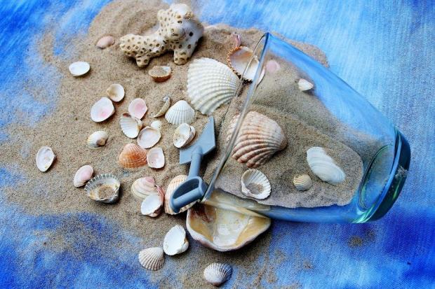 натюрморт из опрокинутого стеклянного стакана и морского песка с ракушками