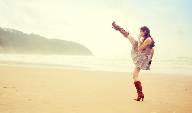 агрессивно настроенная девушка в красных сапогах на пляже