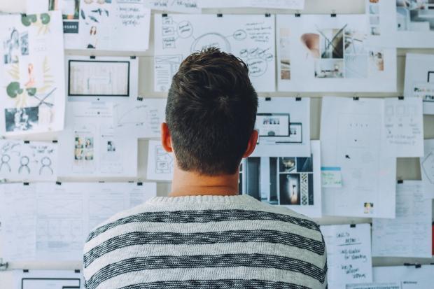 молодой человек смотрит на стену, увешанную разными бумагами