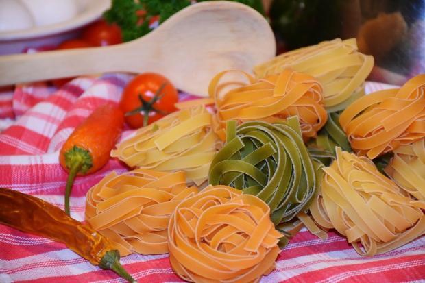 разноцветная лапша и стручки перца лежат на полотенце кв красную полоску