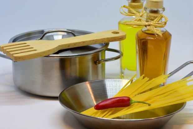 на столе стоит кастрюля оливковое масло и спагетти