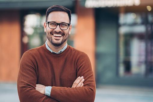 мужчина в очках и коричневом джемпере смеется