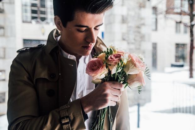 мужчина стоит на улице с букетом нежных роз в руке