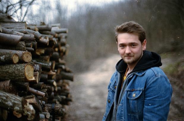 мужчина в джинсовой куртке стоит рядом с поленницей дров