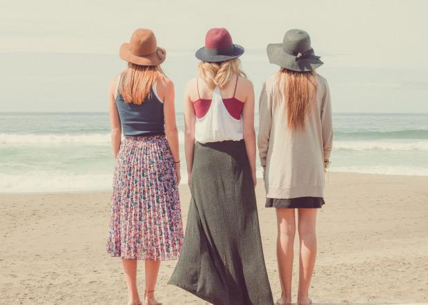 три женщины в шляпках стоит на берегу моря