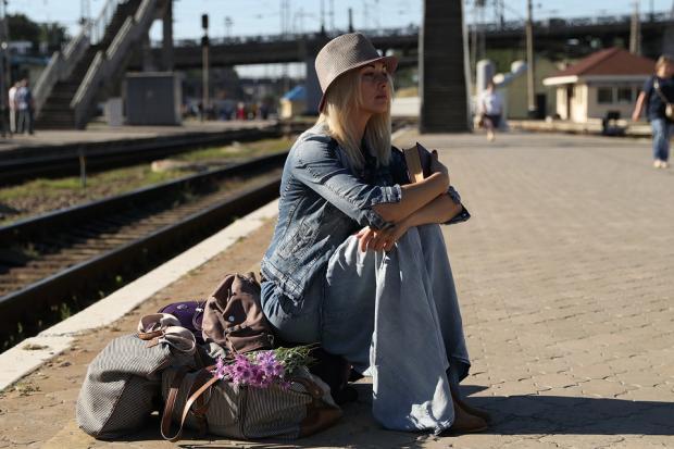 сидящая на перроне вокзала девушка в шляпке