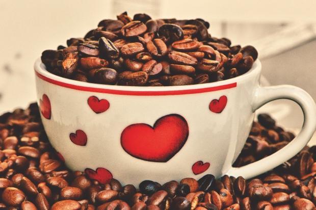 наполненная кофейными зернами белая чашка с рисунками в виде сердца