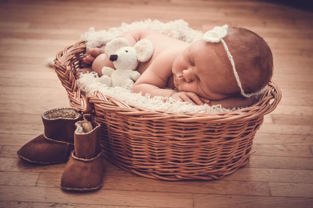 новорожденный спит в плетеной корзинке