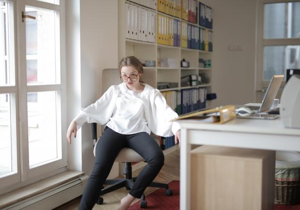 Девушка в белом свитшоте и серых джинсах сидит возле стола