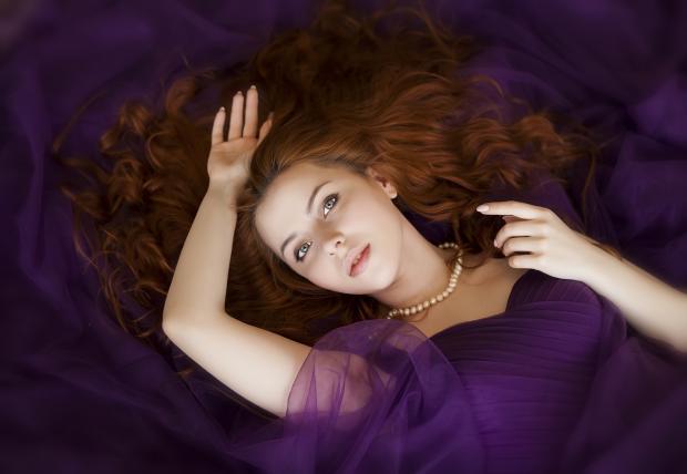 красивая женщина в сиреневом платье с распущенными рыжими волосами