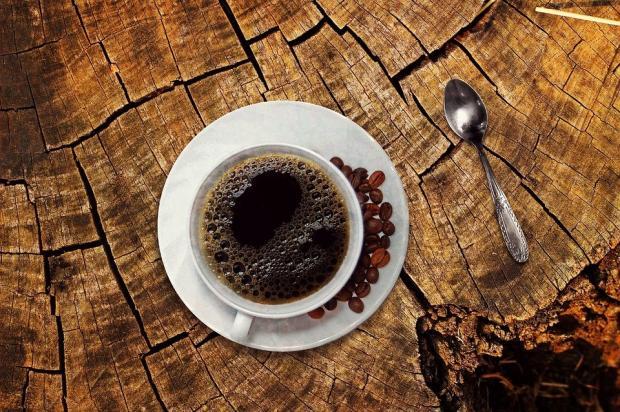 чашка черного кофе стоит на деревянной подставке