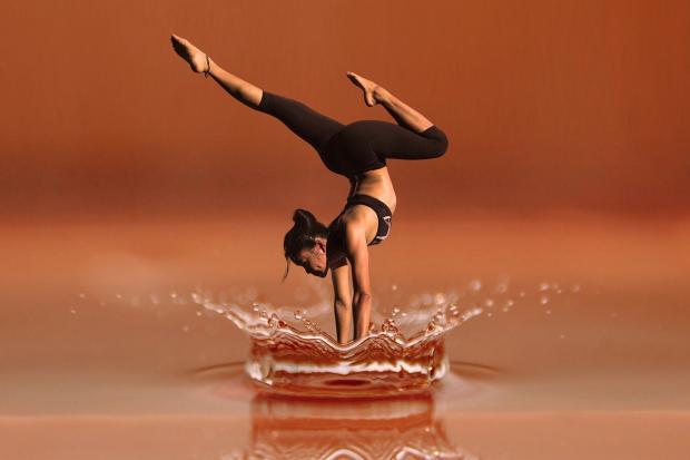 девушка с идеальной фигурой делает йогу в воде