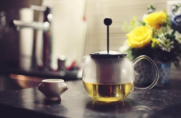 на столе стоит заваренный в стеклянном чайнике зеленый чай