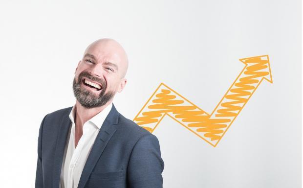 смеющийся мужчина на фона графика направленного вверх