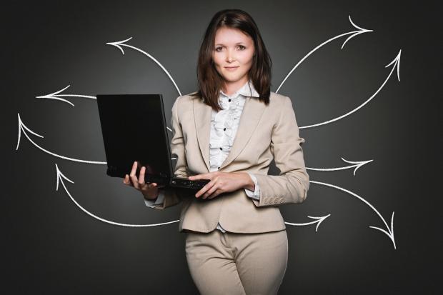 стройная девушка в бежевом костюме с ноутбуком в руках