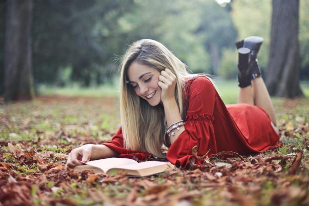 Девушка в красном платье лежит на земле