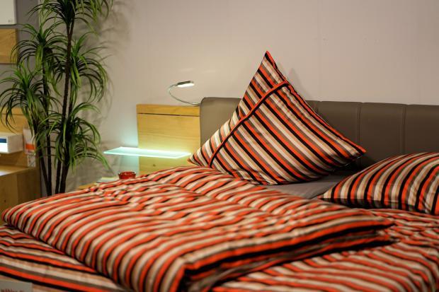 кровать с постельным бельем в полоску