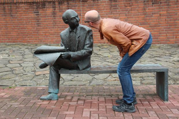 мужчина наклонился к памятнику