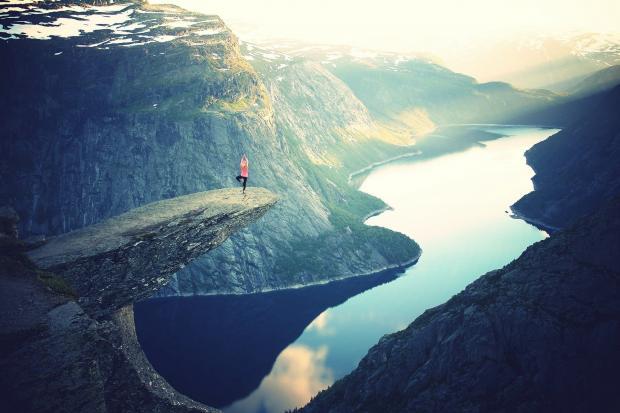 водоем между гор, на скале девушка занимается йогой